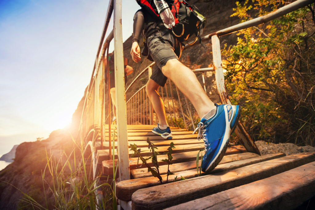 man-hiking-in-mountains-walking-on-wooden-bridge-at-sunset-healthy-lifestyle